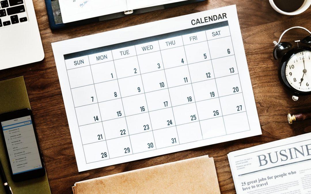 Kalender på skrivbord med laptop och tidning