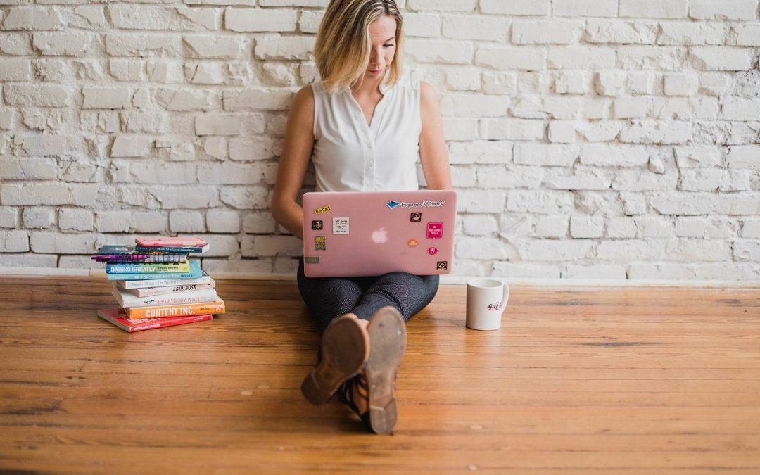 Influencer kvinna med laptop och böcker sitter på golvet
